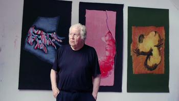 Roland Sénéca devant ses peintures