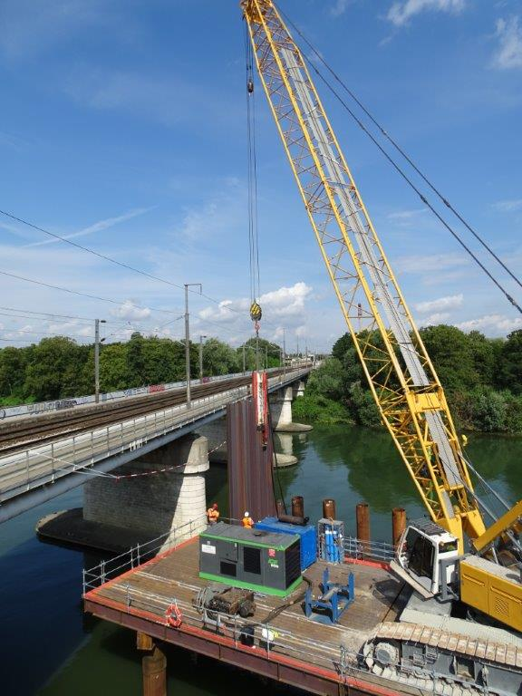Une grue se déplace sur la Seine aux bords d'un pont pour la pose des palpanches