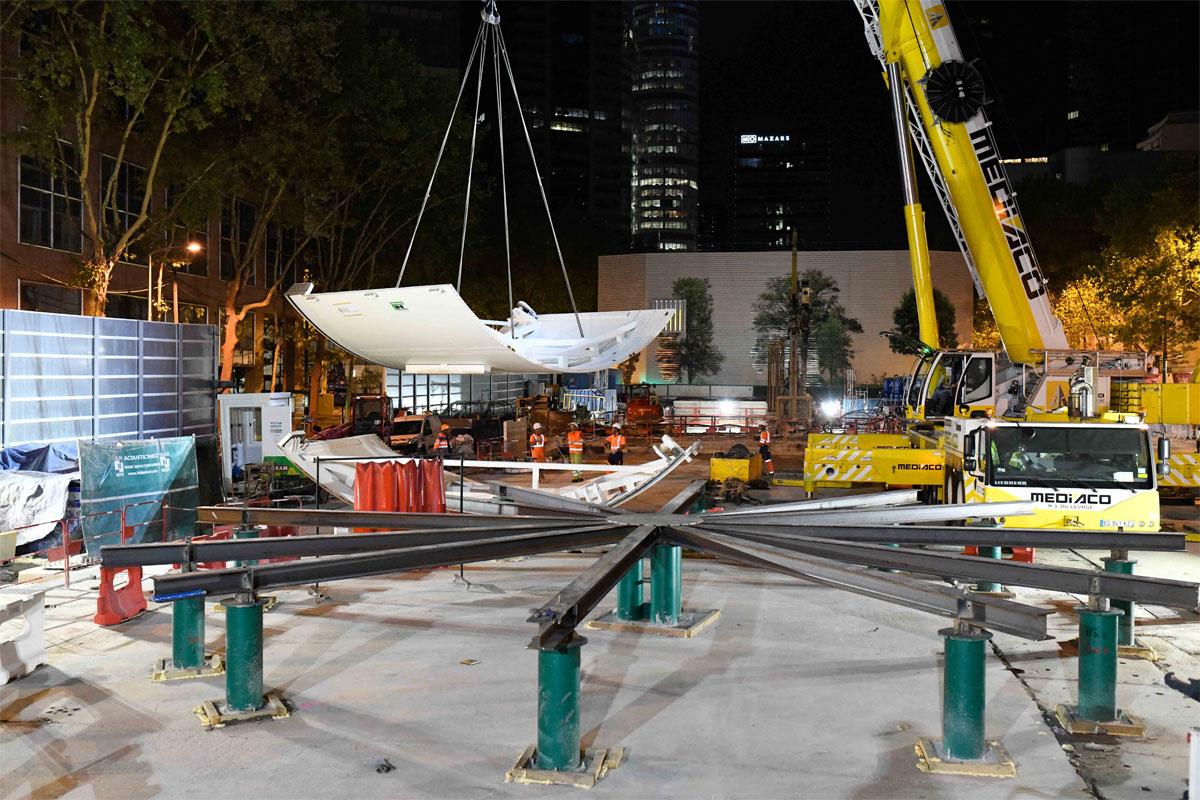 Un morceau du tunnelier est transporté dans las airs à travers un chantier de nuit