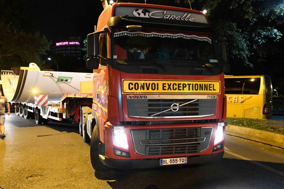 Un camion rouge convoi exceptionnel arrive de face et semble transporter un morceau du tunnelier