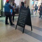 Intérieur d'un hall de gare, un employé SNCF accueil les voyageurs et les informe