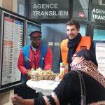 """Hall de gare, deux agents SNCF sont debout devant une table """"mange debout"""", ils proposent des petits déjeuners à une voyageuse devant eux."""