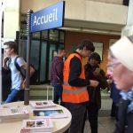 hall de la gare, des agents SNCF informent les voyageurs, une table mange-debout propose des tracts d'informations sur les travaux de prolongement du RER E vers l'Ouest.