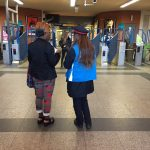 Un agent SNCF de dos échange des informations avec une voyageuse avant de passer les portiques de sécurité.