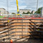Vue du chantier vue du puits, un ouvrier se trouve au fond du puits et tente d'accrocher une barre en fer qui sera soulevée par la grue juste au dessus.
