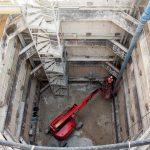 vue d'en haut du puits avec un engin de chantier rouge au fond qui soulève un ouvrier