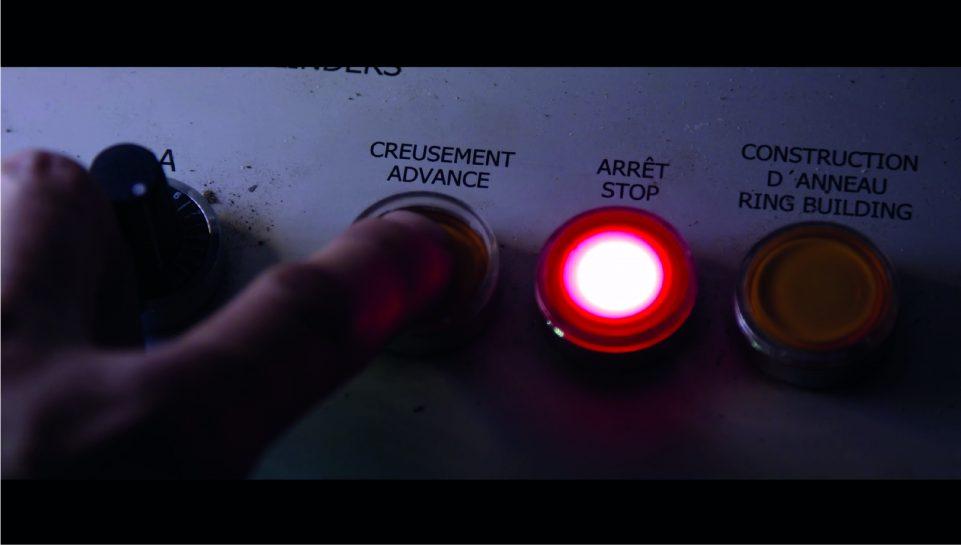 Main qui appui sur le bouton pour lancer le creusement au tunnelier
