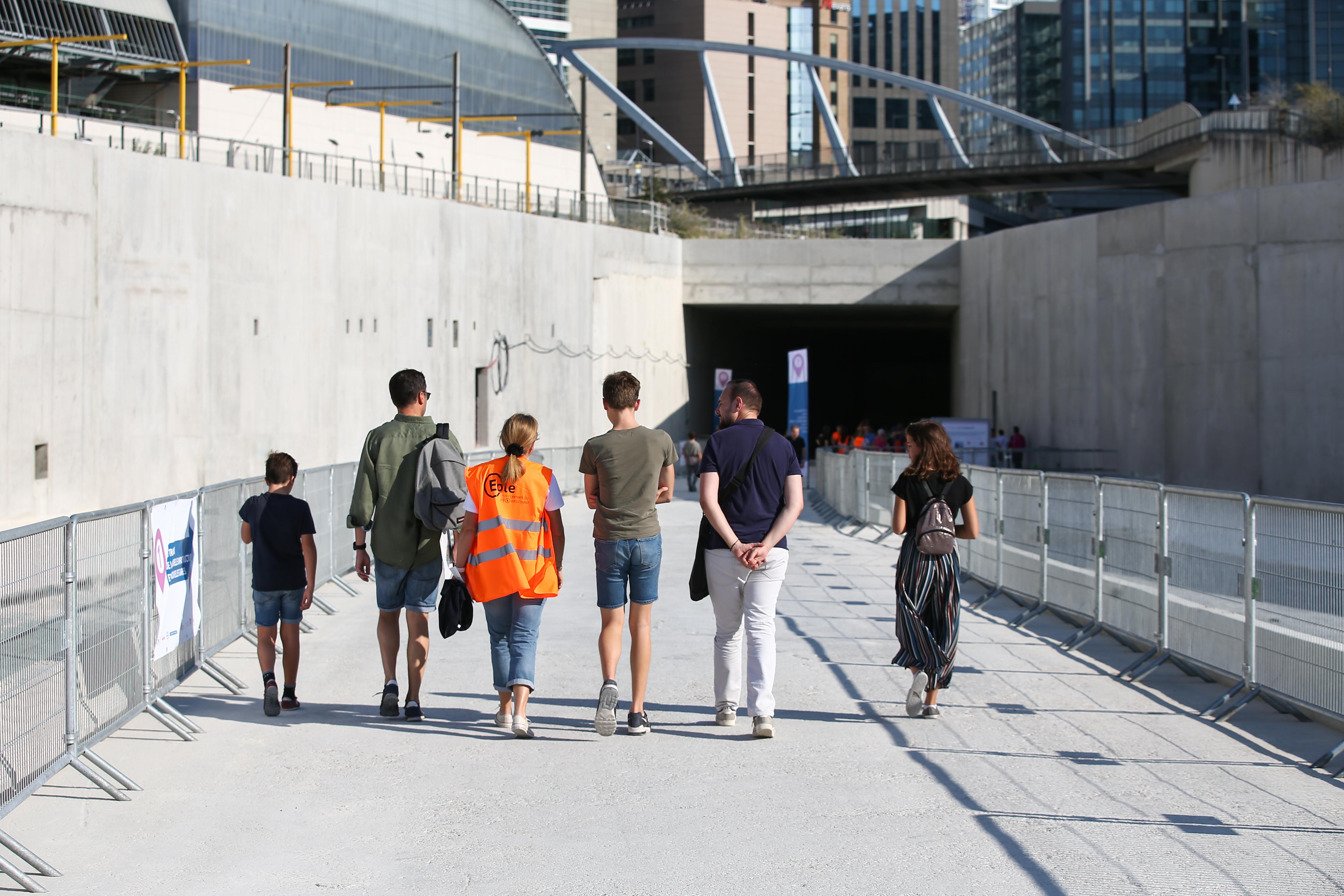 13 photos présentant les visiteurs sur le chantier de la future gare de Nanterre : on y voit des panneaux d'exposition, des engins de chantier, des personnes qui font des visites virtuelles et un groupe de musique.