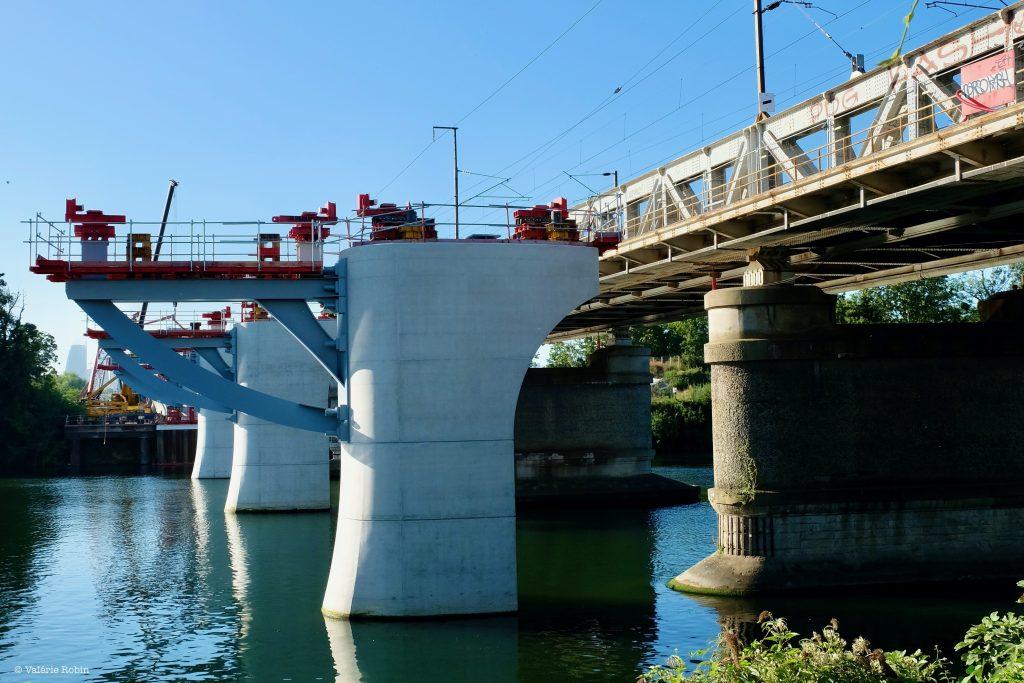 Vue du pont de Bezons rapproché. Le pont reflète dans l'eau qui se tient en bas de l'image. Ciel bleu. Travaux sur le pont.