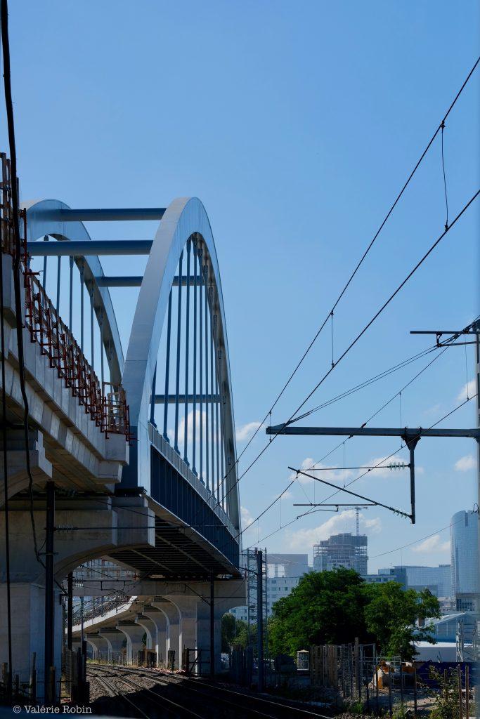 Vue du pont de Bezons en rapproché. Ciel bleu. Travaux sur le pont. Aperçu des rails en bas de l'image.