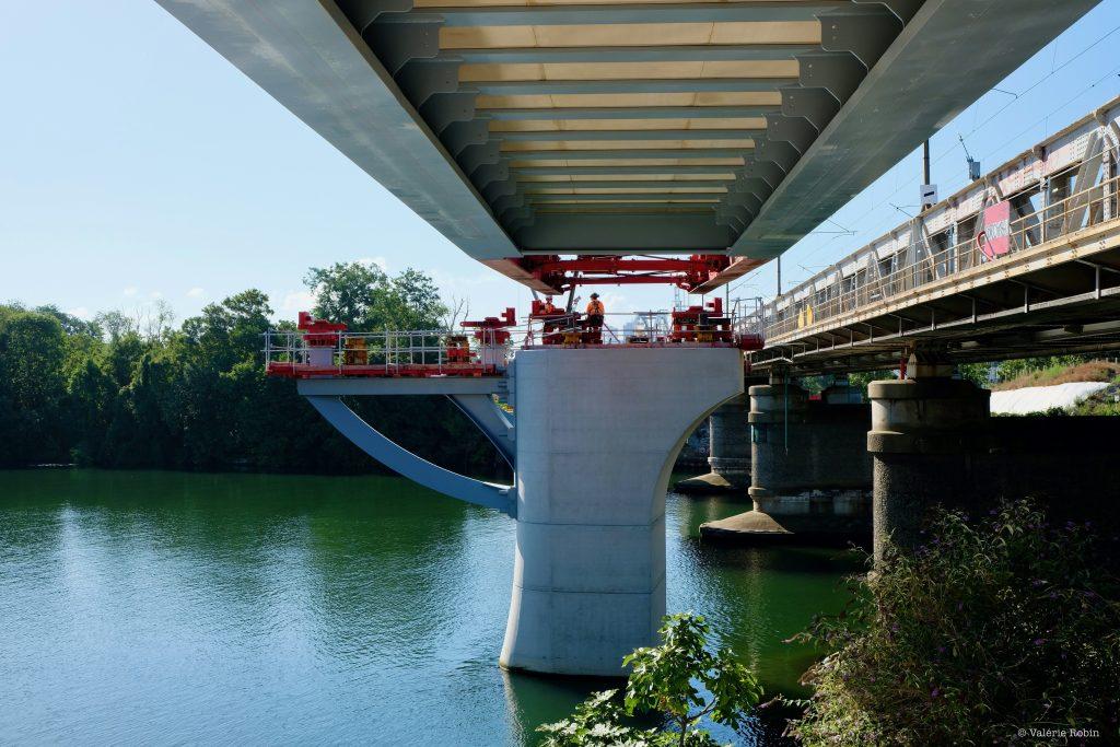 Vue du pont de Bezons en rapproché. Le pont reflète dans l'eau qui se tient en bas de l'image. Ciel bleu. Travaux sur le pont. Des compagnons sont visibles de dos.
