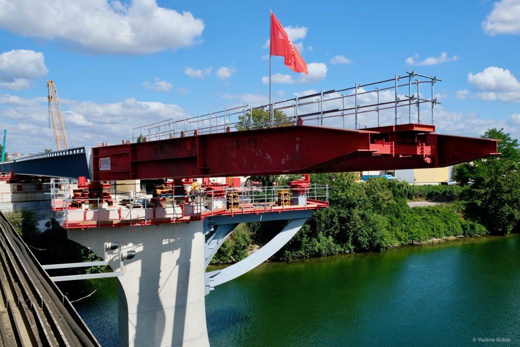 Vue du pont de Bezons. Le pont reflète dans l'eau qui se tient en bas de l'image. Des arbres sur les côtés de l'image. Ciel bleu. Travaux sur le pont.