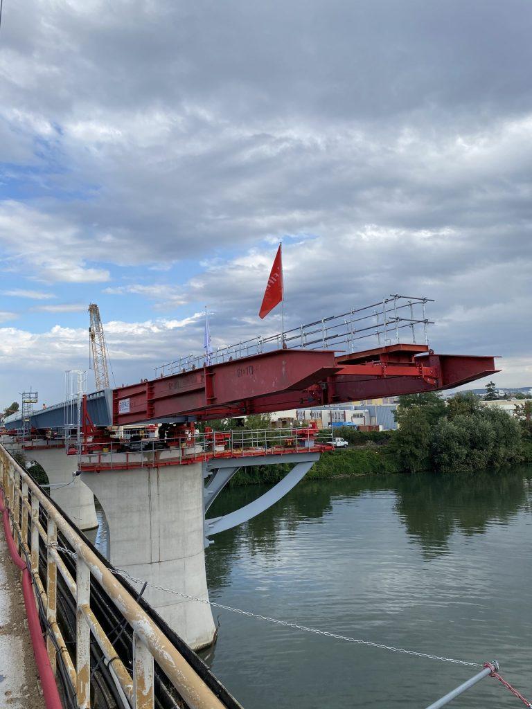 La photo montre le pont rail de Bezons. Le pont est de couleur rouge, il est positionné sur des blocs de béton. En bas de l'image, il y a la Seine.