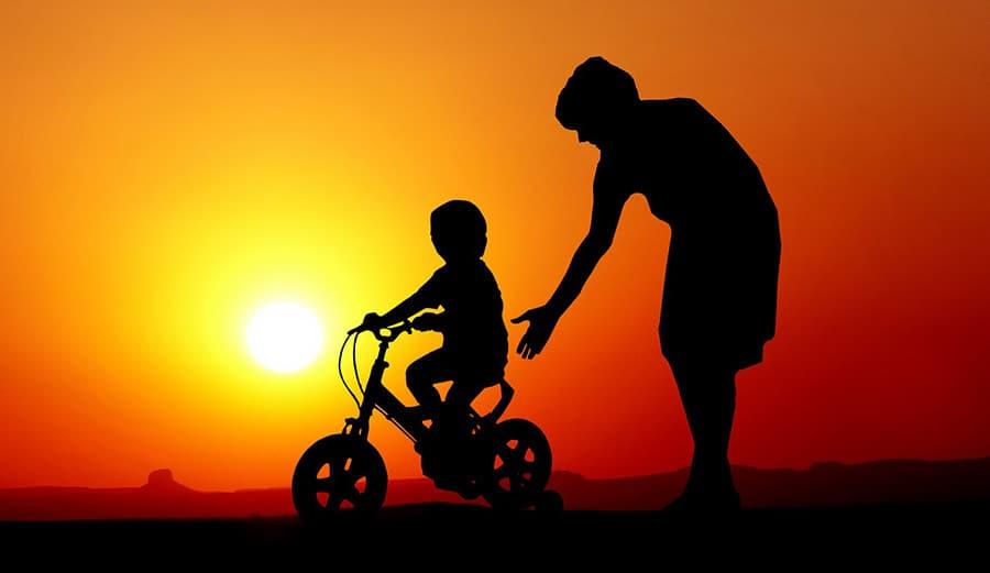 bici bambino e genitore tramonto