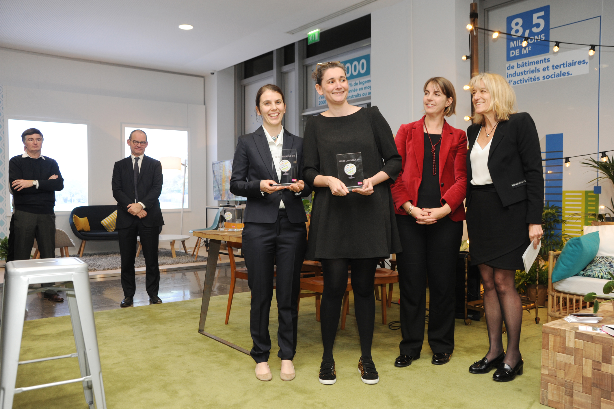 Photo de la remise des prix, on y voit au devant de la scène 4 femmes dont une tenant le trophée dans ses mains