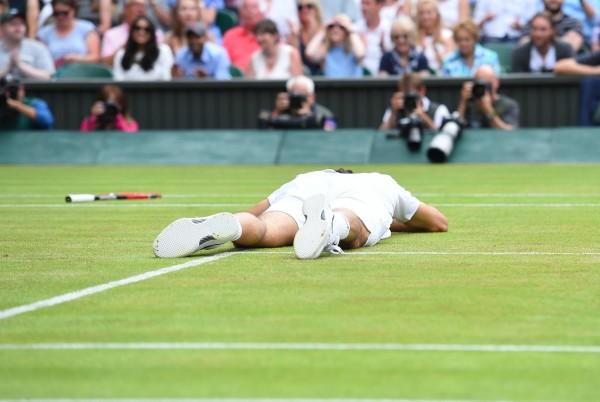 Roger Federer à terre après une mauvaise chute dans le 5e set contre Milos Raonic.
