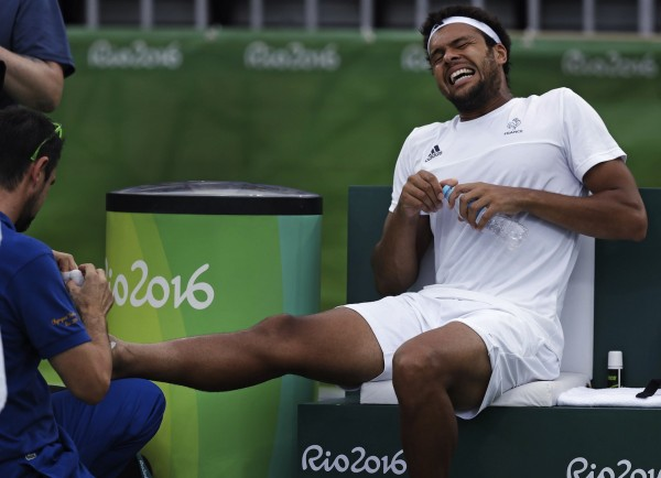 Jo-Wilfried Tsonga, of France, winces in pain as a trainer attends to his injured right foot during a match against Gilles Muller, of Luxembourg, at the 2016 Summer Olympics in Rio de Janeiro, Brazil, Monday, Aug. 8, 2016. (AP Photo/Charles Krupa)/OKRU134/16221695160038/1608082124