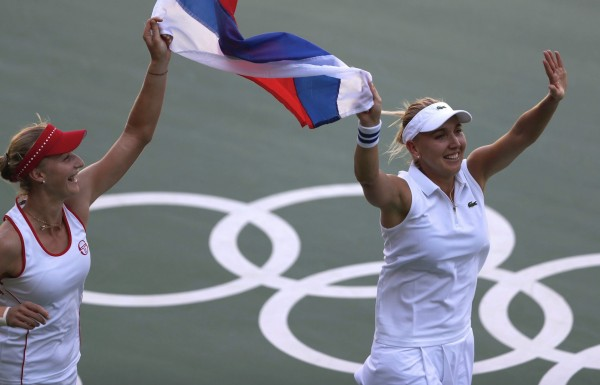 Russia's Elena Vesnina, right, Ekaterina Makarova take a victory lap around center court after defeating Switzerland's Timea Bacsinszky and Martina Hingis during the final of the women's doubles tennis competition at the 2016 Summer Olympics in Rio de Janeiro, Brazil, Sunday, Aug. 14, 2016. (AP Photo/Vadim Ghirda)/OVG105/16227665331883/1608142035