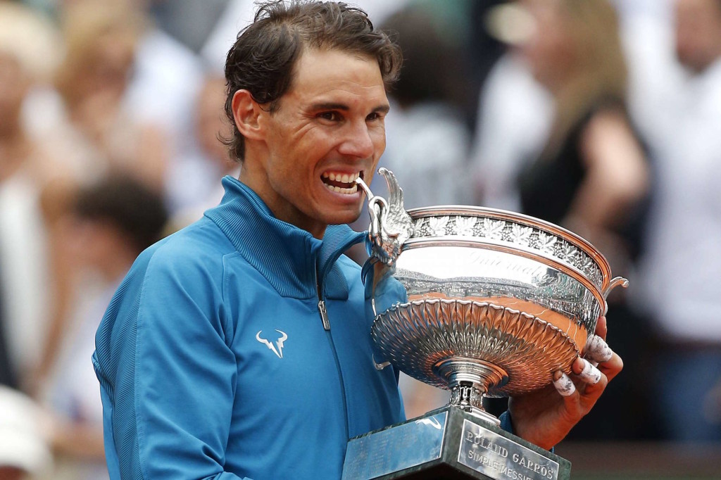 Spain's Rafael Nadal bites the cup the after defeating Austria's Dominic Thiem in the men's final match of the French Open tennis tournament at the Roland Garros stadium, Sunday, June 10, 2018 in Paris. Nadal won 6-4, 6-3, 6-2. (AP Photo/Thibault Camus)/ROG167/18161591399353/1806101828